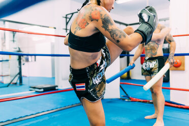 Male and female boxers working out in boxing ring - CUF48411