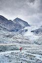 Hiker moving across rocky terrain, Mont Cervin, Matterhorn, Valais, Switzerland - CUF48450