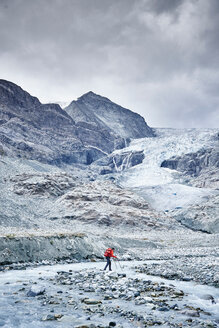 Hiker moving across rocky terrain, Mont Cervin, Matterhorn, Valais, Switzerland - CUF48450