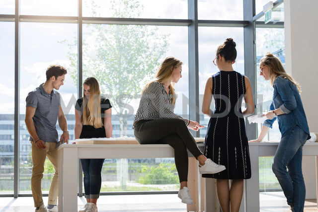 Colleagues brainstorming by glass wall - CUF48462