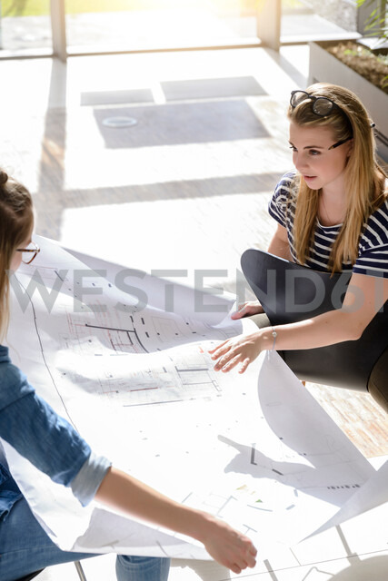 Colleagues brainstorming over charts in bright sunlight - CUF48486