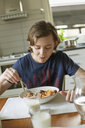 Teenage boy eating breakfast in a house - FOLF10248