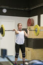 Young woman lifting a barbell in a gym - FOLF10272
