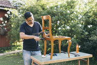 Mid adult man repairing a chair outdoors in Kvarnstugan, Sweden - FOLF10275
