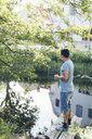 Mid adult man standing next to a river in Mortfors, Sweden - FOLF10278
