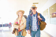Young couple at airport, carrying backpacks, setting off on journey - ISF20120