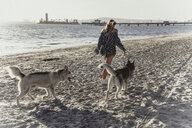 Young woman walking pet dogs on beach - ISF20132