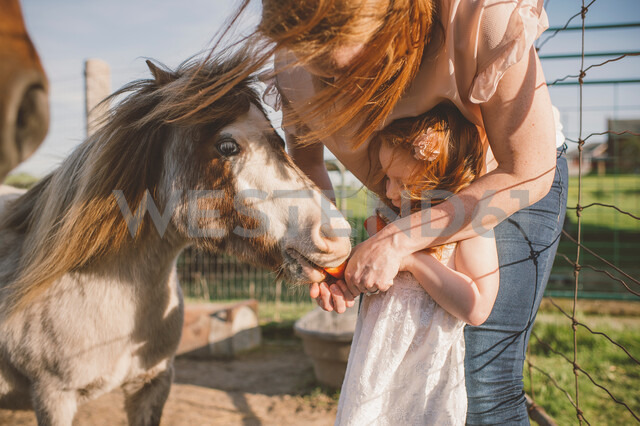 Mother and daughter feeding pony in farm - ISF20141
