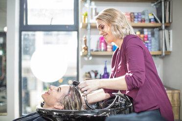 Hairdresser rinsing customer's hair in salon - ISF20144