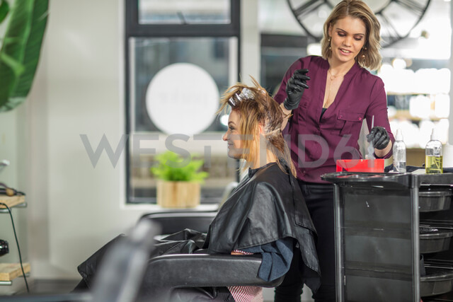 Hairdresser colouring customer's hair in salon - ISF20153
