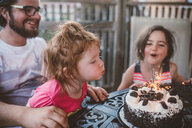 Female toddler with sister and father blowing out sparklers on celebration cake at patio table - ISF20186