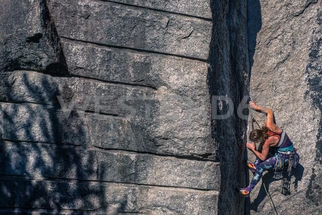 Young female rock climber climbing rock face, Smoke Bluffs, Squamish, British Columbia, Canada - ISF20192