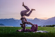 Two young women practicing acroyoga on grass in front of mountain range at sunset, Squamish, British Columbia, Canada - ISF20195