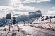 Rural road in snow capped mountains, Dolomites, Italy - ISF20198