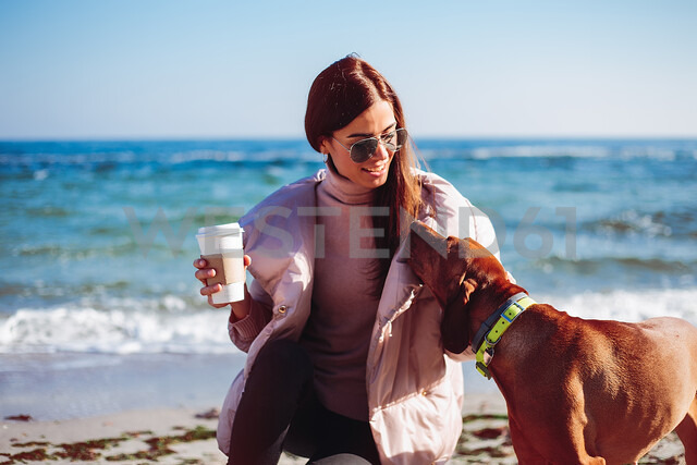 Stylish mid adult woman crouching on beach petting her dog, Odessa, Odeska Oblast, Ukraine - ISF20210