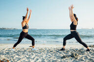 Friends doing exercises on beach, Long Beach, California, US - ISF20216