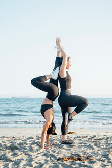 Friends doing exercises on beach - ISF20219