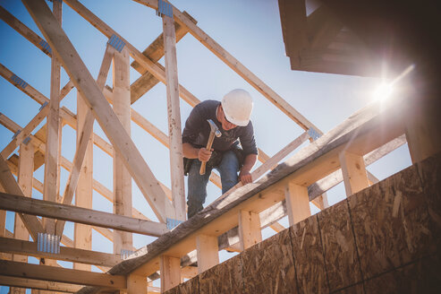 Builder working on rooftop frame of building - ISF20258