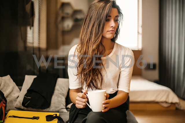 Woman with cup contemplating in bedroom - ISF20261