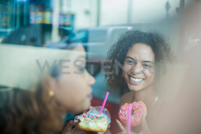 Girlfriends having doughnuts in cafe - ISF20267