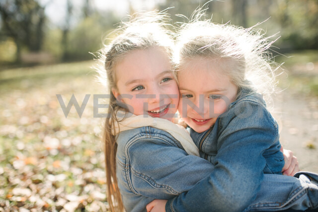 Sisters hugging in forest - ISF20315