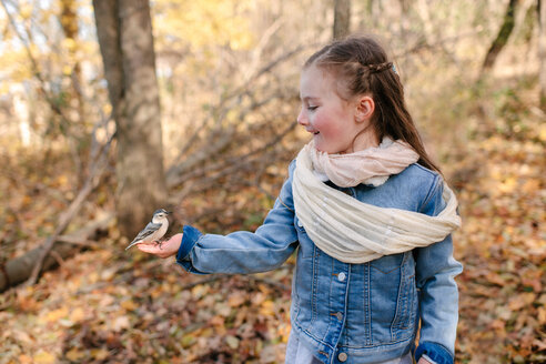 Little girl holding bird on palm in forest - ISF20318
