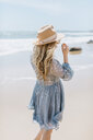 Young woman on windy beach, rear view, Menemsha, Martha's Vineyard, Massachusetts, USA - ISF20345