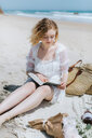 Young woman reading book on beach, Menemsha, Martha's Vineyard, Massachusetts, USA - ISF20351