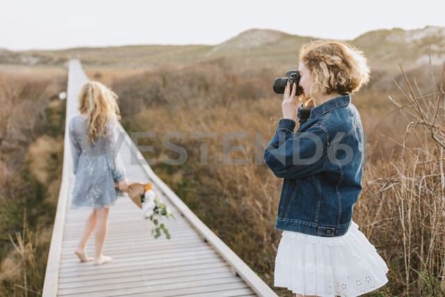 Young woman photographing friend on coastal dune boardwalk,  Menemsha, Martha's Vineyard, Massachusetts, USA - ISF20360