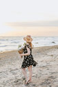 Young woman with bunch of flowers on windy beach, Menemsha, Martha's Vineyard, Massachusetts, USA - ISF20363
