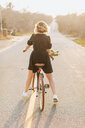 Young woman riding bicycle on rural road, rear view, Menemsha, Martha's Vineyard, Massachusetts, USA - ISF20366