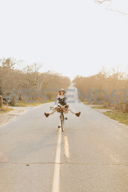 Young woman riding bicycle with legs raised on rural road, Menemsha, Martha's Vineyard, Massachusetts, USA - ISF20369