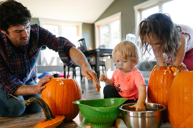 Father and children gutting pumpkin at home - ISF20387