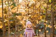 Falling autumn leaves in front of little girl in forest - ISF20393