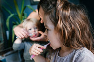 Mother helping children brush teeth - ISF20396