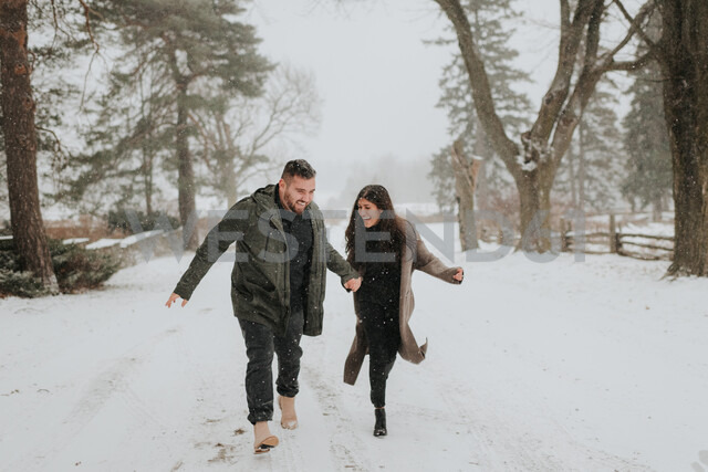 Couple running in snowy landscape, Georgetown, Canada - ISF20399