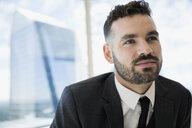 Pensive businessman looking away at urban office window - HEROF05453