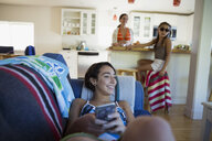 Mother and daughters relaxing in kitchen and living room - HEROF05468