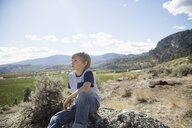 Pensive boy sitting on rock looking at sunny rural view - HEROF05525