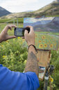 Male painter photographing sunflower painting with camera phone in rural field - HEROF05534
