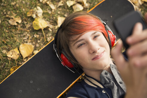 Overhead view boy with dyed red hair laying on skateboard using cell phone in autumn leaves - HEROF05567
