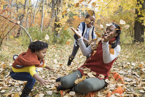Mother and daughters playing throwing autumn leaves in park - HEROF05579