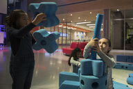 Girls stacking and connecting large peg and pieces in science center - HEROF05624