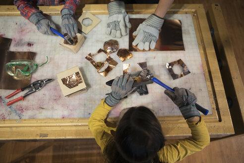 Overhead view girl hammering metal in science center workshop - HEROF05633