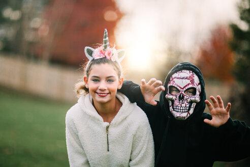 Siblings in halloween costume posing in park - ISF20465