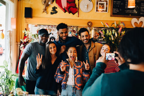 Young man photographing cheerful multi-ethnic friends standing at restaurant during brunch - MASF10865