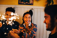 Cheerful young multi-ethnic friends sitting with burning sparklers at restaurant - MASF10877