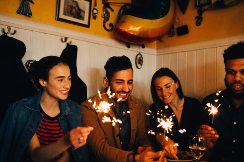 Happy young multi-ethnic male and female friends holding burning sparklers in restaurant during dinner party - MASF10880