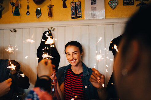 Smiling young multi-ethnic friends holding burning sparklers while enjoying in restaurant during dinner party - MASF10883