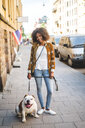 Portrait of smiling mid adult woman standing with dog on sidewalk in city - MASF10925
